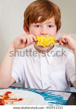 A young caucasian boy looking at the camera eating corn on the cob