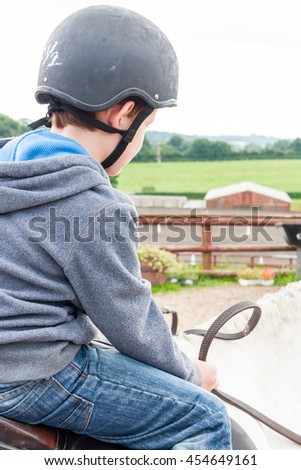 A young caucasian boy sat on top of a white pony whilst holding the reins
