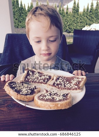 A young Caucasian boy with a plate of bread, chocolate spread and sprinkles