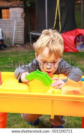 A young caucasian boy with blond hair playing outside in a garden with a water table