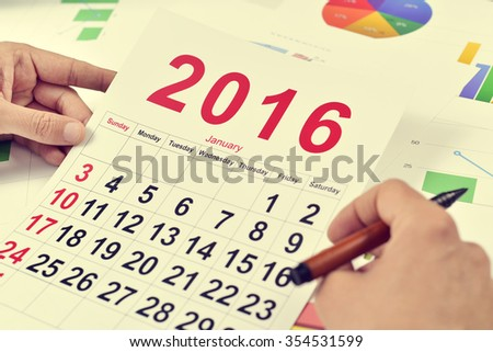 a young caucasian businessman at his office desk full of charts observes a 2016 calendar - stock photo