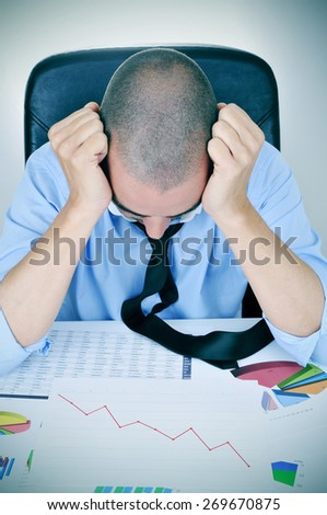 a young caucasian businessman in his office desk full of graphs and charts observing worried a chart with a downward trend - stock photo