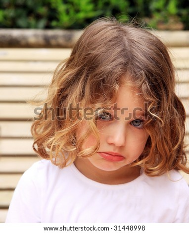 a young caucasian child with a pretty face sulking and pouting against a natural background - stock photo