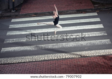 A Young Caucasian female ballerina dancing on a zebra crossing