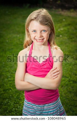 A young Caucasian girl stands in the sunshine and smiles at the camera. - stock photo
