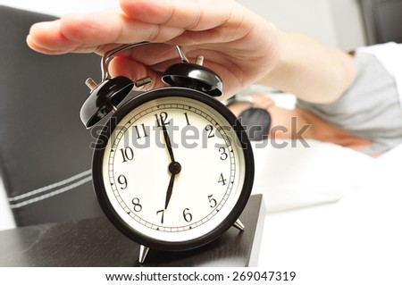a young caucasian man in bed with a sleep mask stops the alarm clock at 7 in the morning - stock photo