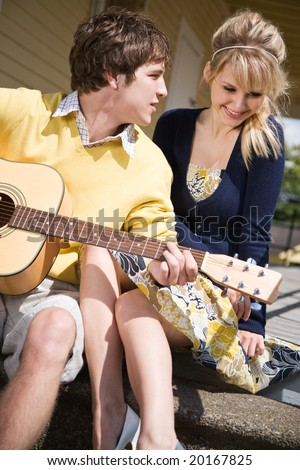 A young caucasian man playing guitar and sings to his girlfriend - stock photo