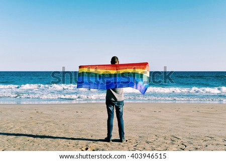 a young caucasian man seen from behind extending a rainbow flag in front of the ocean - stock photo