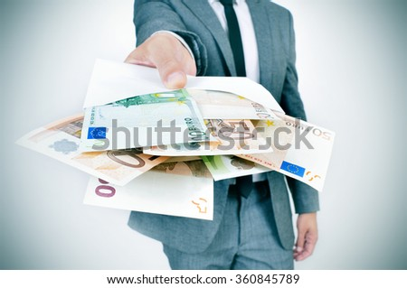 a young caucasian man wearing a gray suit gives an envelope full of euro bills to the observer - stock photo