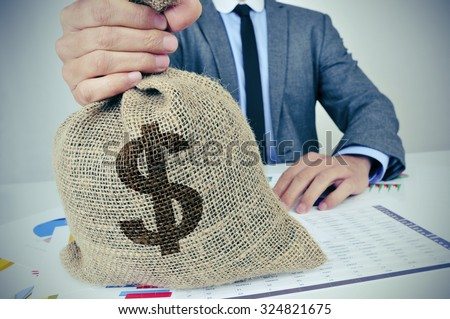 a young caucasian man wearing a gray suit seated at an office desk full of charts and financial balances holds a burlap money bag with the US dollar currency sign in his hand - stock photo