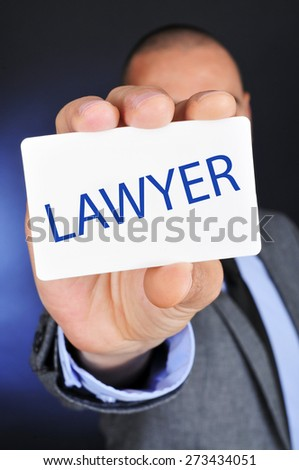 a young caucasian man wearing a gray suit shows a signboard with the word lawyer written in it - stock photo
