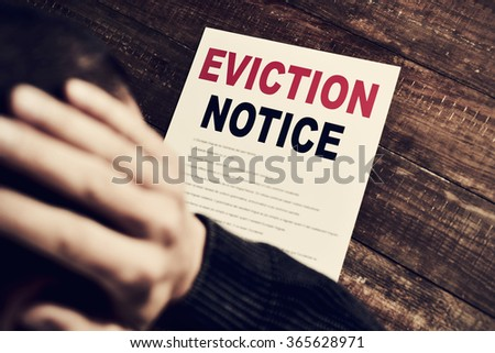 a young caucasian man with his hands in his head concerned because has just received an eviction notice - stock photo