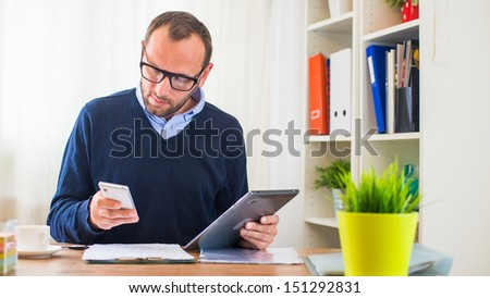 A young caucasian man with tablet and phone in his office. - stock photo