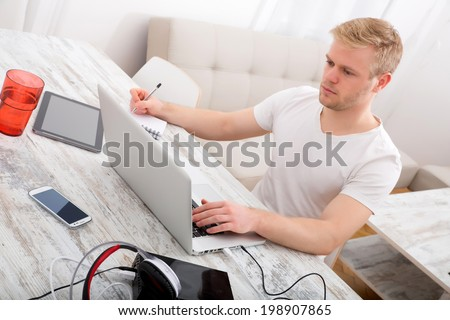 A young caucasian man working in his home office. - stock photo