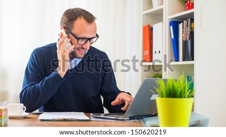 A young caucasian man working on a desk with a laptop and mobile phone. - stock photo