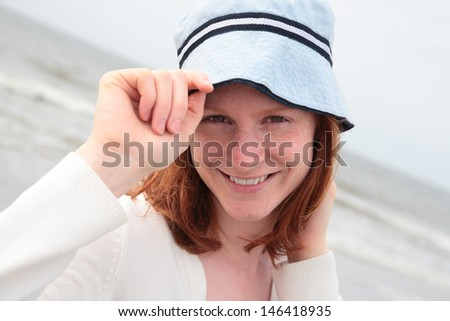 A young Caucasian woman in her 20s having some fun free time on the beach. Photographed while looking at the camera and holding her hat. - stock photo
