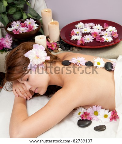A young Caucasian woman lies on a massage table with hot stones on her back and candles and flowers surrounding her. - stock photo