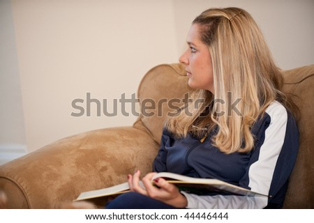 A young Caucasian woman relaxing on a couch with her dog and book - stock photo