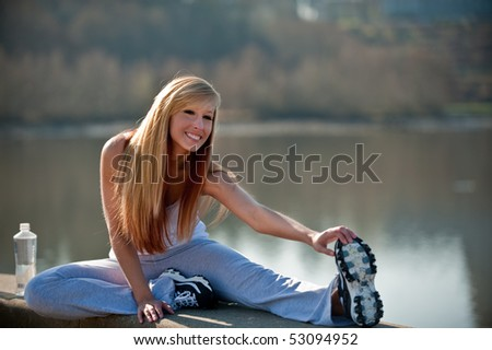 A young Caucasian woman stretching by the lake