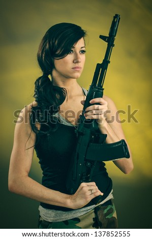 A young caucasian woman with an assault rifle.