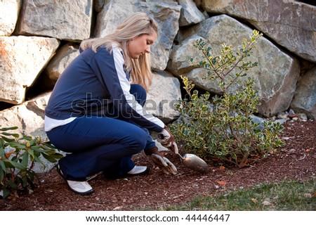 A young Caucasian woman working on her backyard garden - stock photo