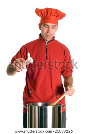 A young chef adding some salt to his pot of soup, isolated against a white background - stock photo