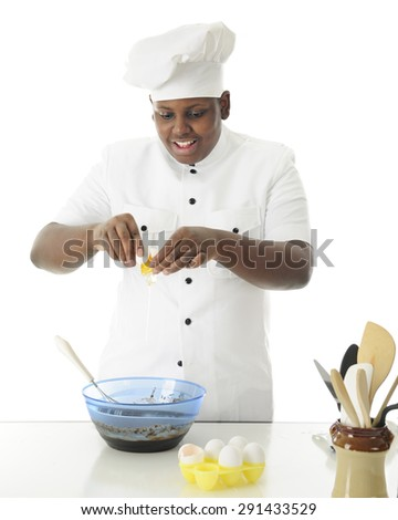 A young chef breaking an egg into the brownie batter he's making.  On a white background. - stock photo