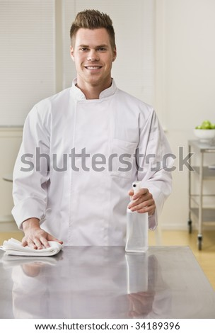 A young chef is cleaning the counter in a kitchen and smiling at the camera.  Vertically framed shot. - stock photo