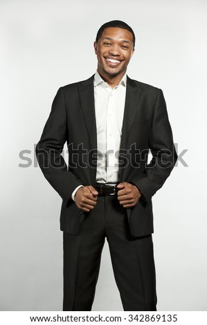 A young chic black male laughing while wearing white button down shirt with a custom suit jacket in a studio setting on a white background. - stock photo