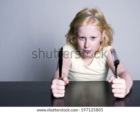 A young child awaits a meal with knife and fork in hand. - stock photo