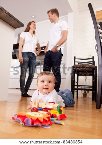 A young child boy playing on the kitchen floor with happy parents talking in the background - stock photo