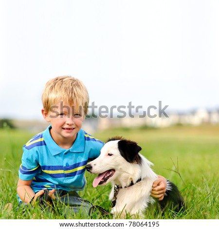 A young child in a field with his pet dog - stock photo