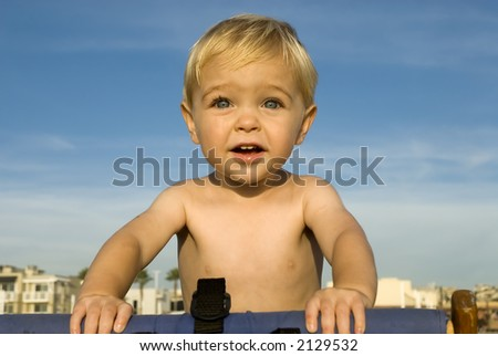 a young child is at the beach and looking out to sea - stock photo