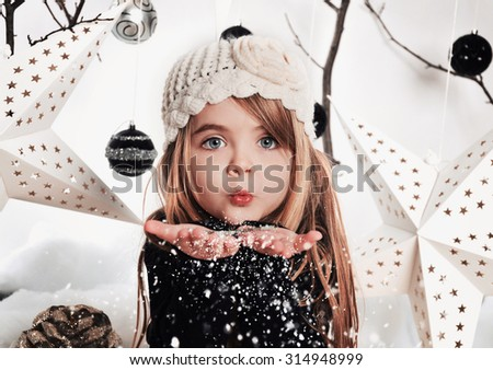 A young child is blowing white snowflakes in a studio background scene with stars and Christmas ornaments for a holiday concept. - stock photo