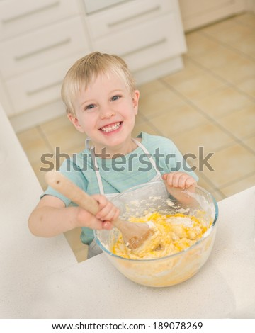 A young child is cooking in a domestic kitchen.  He is mixing the ingredients of a cake in a bowl with a wooden spoon. The small boy is smiling and looking at the camera.