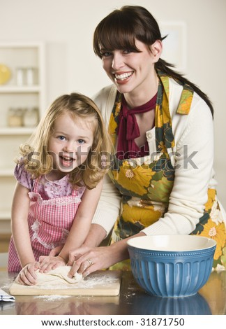 A young child is helping a woman knead some dough to make bread.  They are smiling at the camera.  Vertically framed shot. - stock photo
