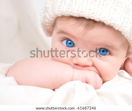 A young child is looking into the camera and sucking their hand. The baby is wearing a hat and has bright blue eyes. Use it for a parenting or love concept.