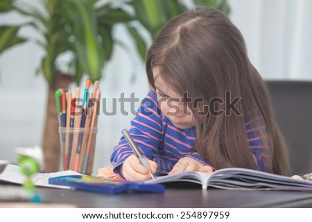A young Child is Painting on a coloring book. The young girl is looking very interested in drawing.