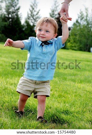 A young child is standing on the grass.  The mother is helping the child walk.  The baby is smiling and looking away from the camera.  Vertically framed shot. - stock photo