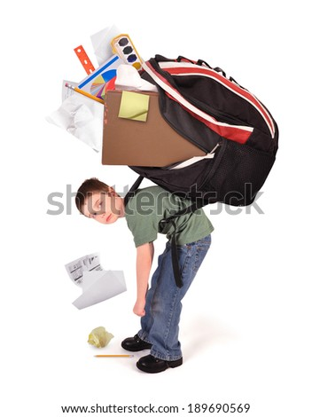 A young child is standing with a large heavy school book bag on his back for a homework or stress concept on a white background. - stock photo