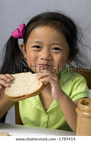 A young child makes a peanut butter and Jelly sandwich - stock photo