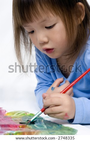A young child paints her masterpiece while laying on the floor. - stock photo