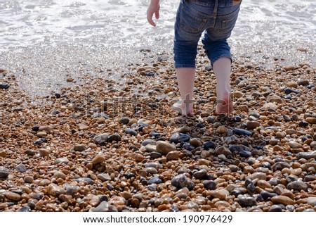 A young child playing on the shoreline of a pebble beach - stock photo