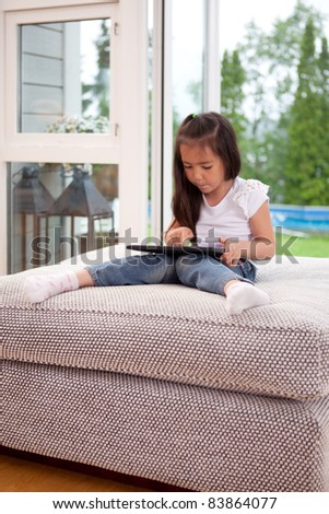 A young child playing with a digital tablet in a living room interior - stock photo