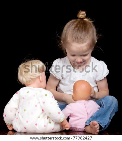A young child plays with her dolls.  She is having too much fun!