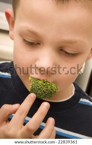 A young child puts a piece of broccoli in his mouth