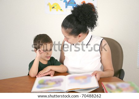 A young child reads a book with help from a teacher or tutor - stock photo