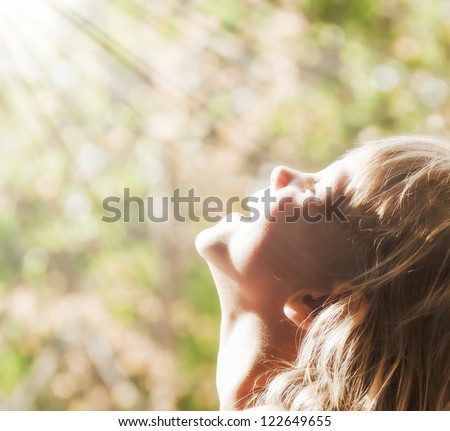 A young child smiling rays of the sun - stock photo