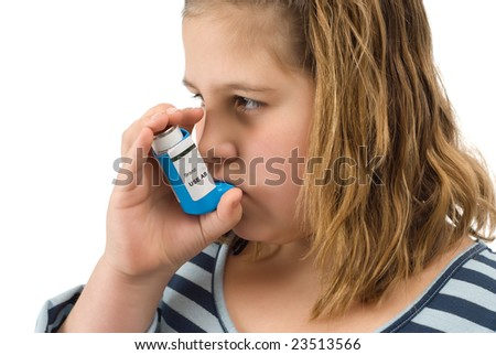 A young child taking her asthma inhaler, isolated against a white background