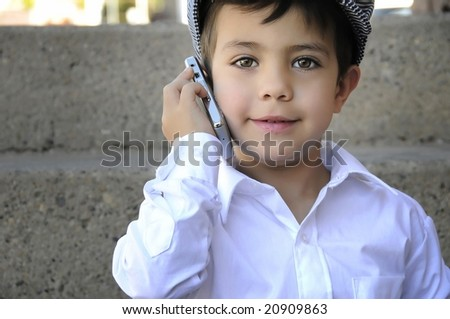 a young child talking on his cell phone - stock photo